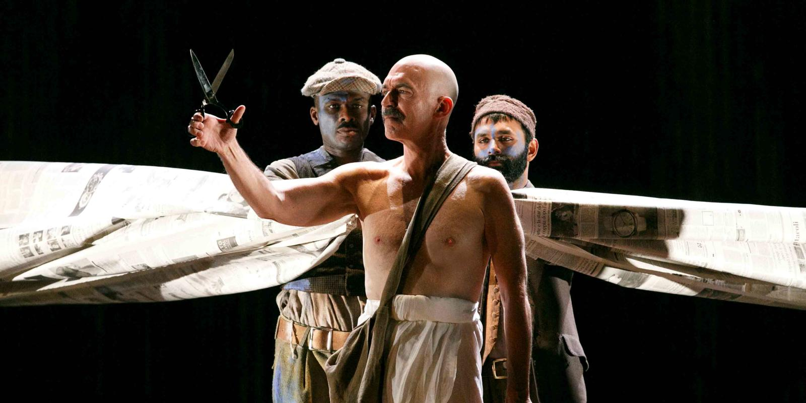An image of Alan Oke and members of skills ensemble in Phelim McDermott's 2013 production of Satyagraha
