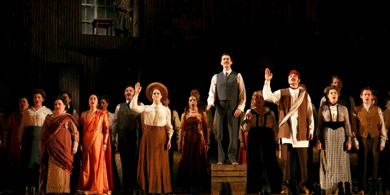 An image of Alan Oke, Clare Eggington, Nicholas Masters and members of the ENO Chorus in Phelim McDermott's 2013 production of Satyagraha