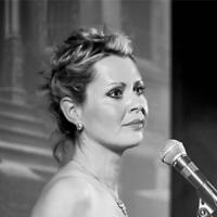 Joanna Appleby singing into a microphone