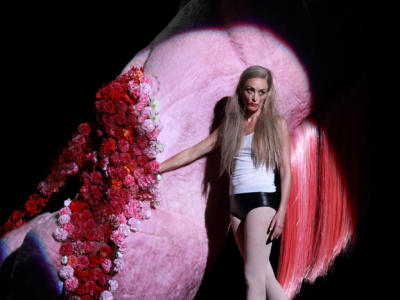 Alison Cooke as Salome wearing black leather underwear stood with her hand inside a giant decapitated pink pony with flowers in place of blood