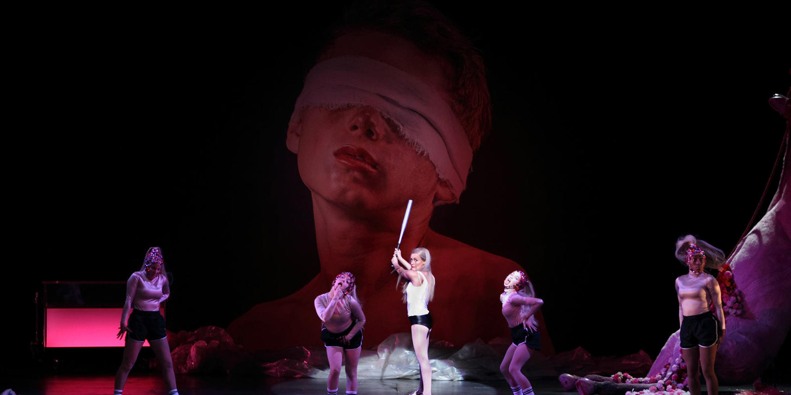 Salome title role posed with a baseball bat surrounded by dancers wearing sporting gear and sparkly headbands