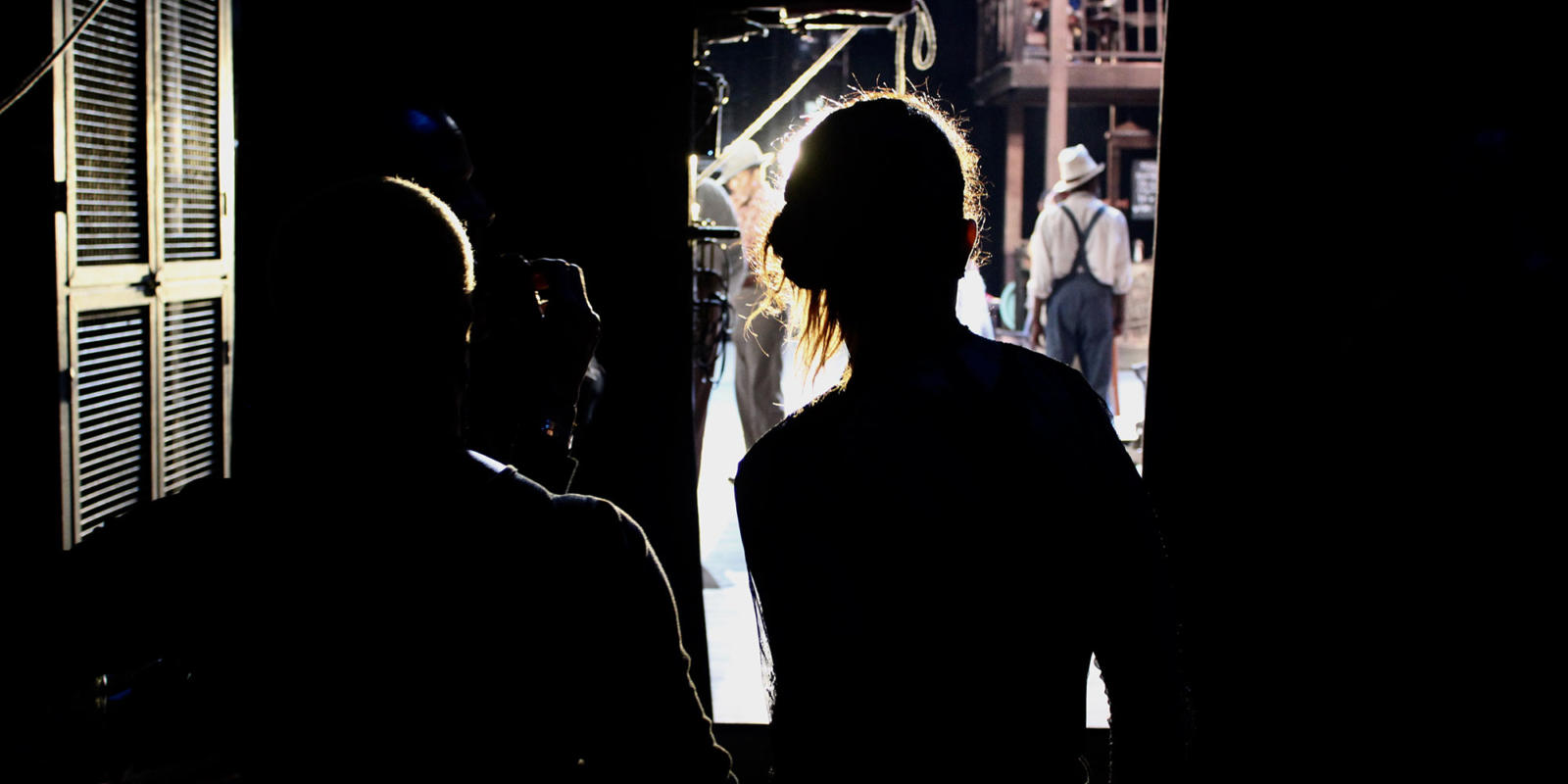 Members of the Stage Management Team look on at the performance from the wings