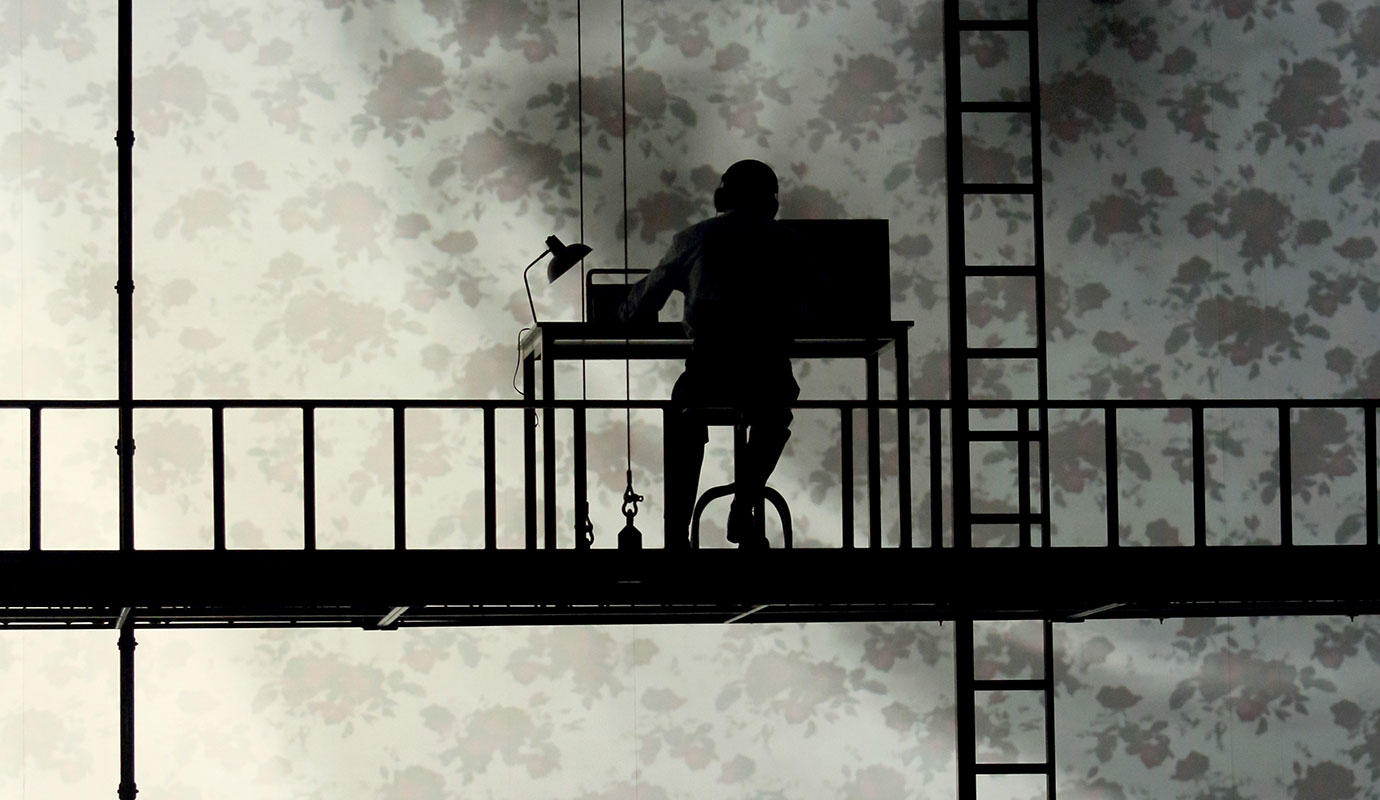 2 versions of Orphée work as desks, silhouetted agaisnt a projected backdrop.