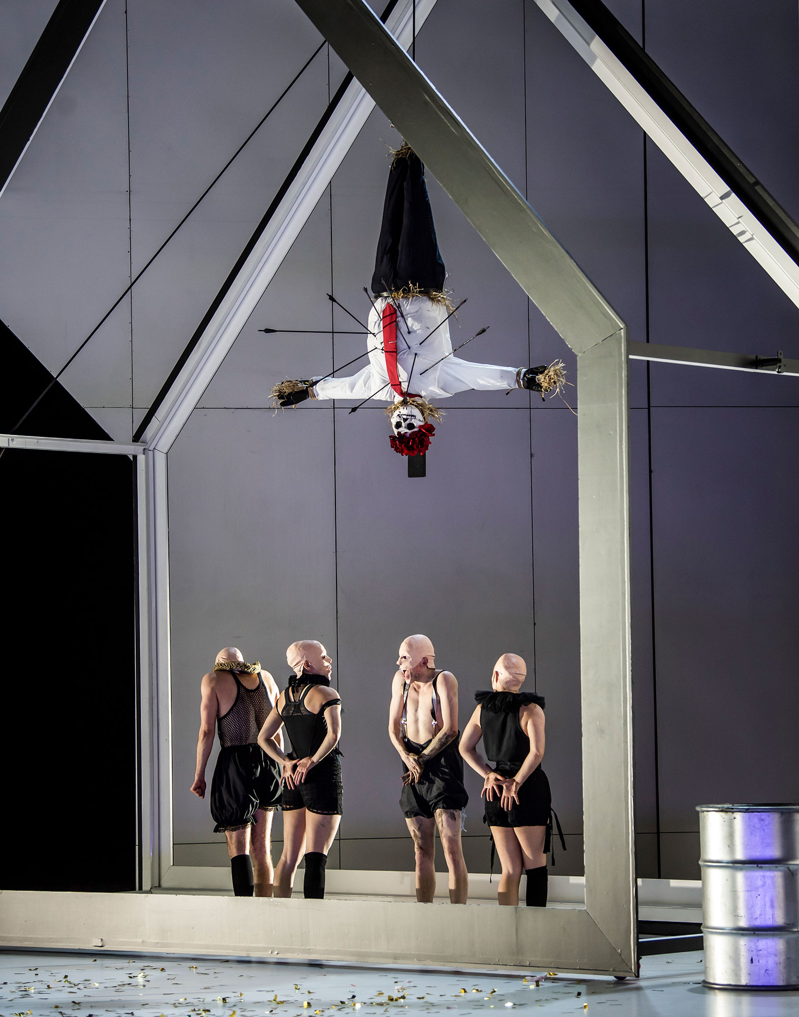 Dancers stand under a scarecrow hanged upside down, pierced by arrows