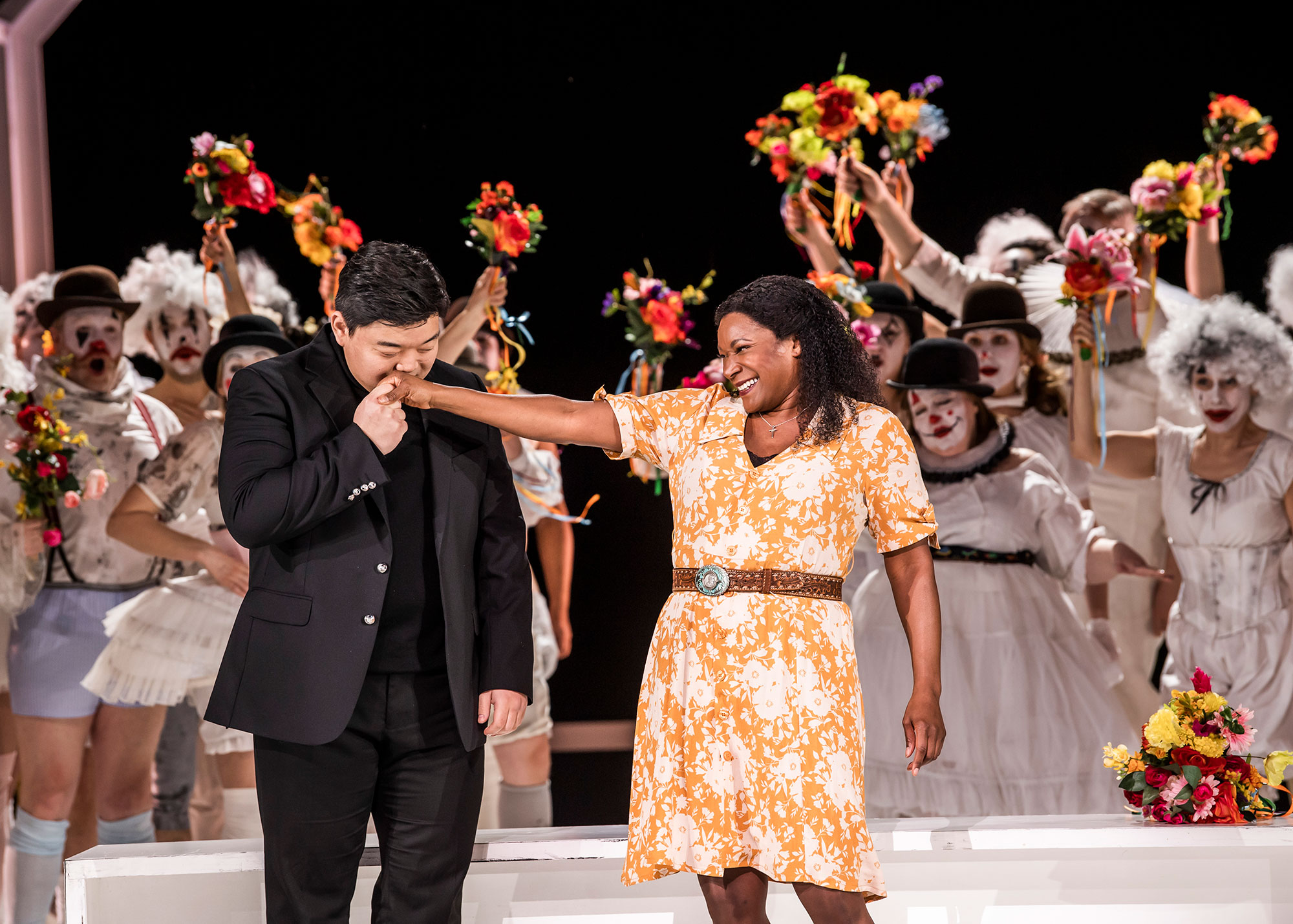 Rodolfo kisses Luisa's outstretched arm, with a macabre crowd holding flowers behind