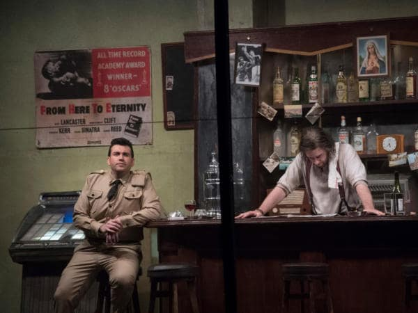 soldier sitting at bar with barman keeping his head down